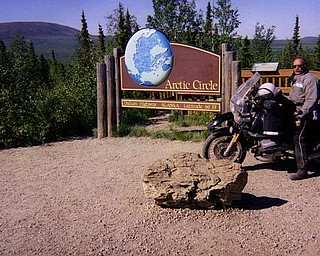 Roy Dyckman poses on his motorcycle in front of a sign along the Dalton Highway in Alaska to the Arctic Circle.