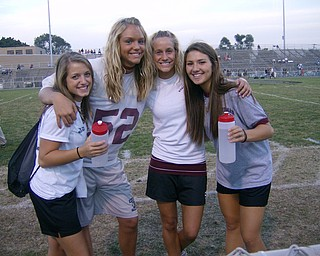 Spartan trainers Courtney Ivan, Courtney Schiffauer, Melanie Sfara, and Monica Touvelle, who all play sports, help out the Football team by filling up the water bottles before the big game.