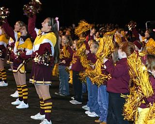 """South Range cheerleaders are helped by the elementary cheerleaders on the sideline for the last regular season."""