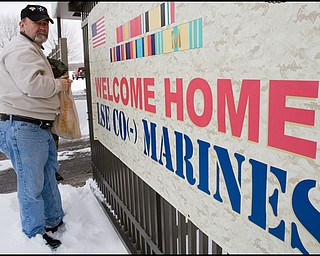 3.22.2008 Kerry Wesp, of Rocky River, hangs a sign in support of 23 returning marines, including his son, Sgt. Chris Wesp at the Youngstown Air Reserve Station in Vienna.