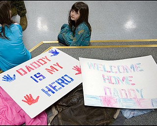 3.22.2008 Liliana Norris, age 5 of Hermitage, sits beside signs made in anticipation of her father's return from a seven month deployment in Iraq at the Youngstown Air Reserve Station in Vienna.