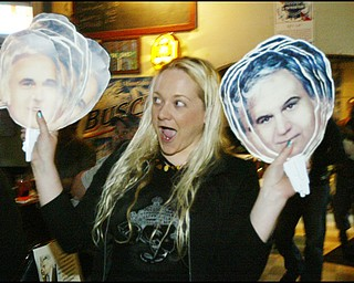 "Jess McElhinny of Youngstown passes out ""Jimmy's on a stick"" cutout faces of former congressman, Jim Traficant, during a birthday party Thursday."