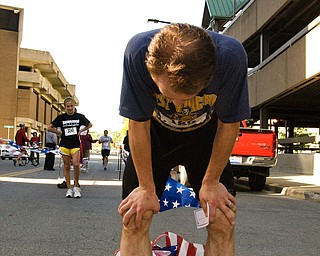 Amun Rigstad, 34, of Youngstown takes a deep breath after finishing the race in just over 32 minutes. With over 300 people in attendance, the finish line at the YMCA's annual five-mile run offered a look at the people who jog these valley walls.