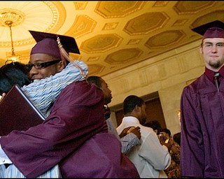 6.1.2008 Nathaneil Byrd III. stops for a hug as Adam Carpenter and his fellow graduating seniors from Liberty High School exit Stambaugh Auditorium Sunday afternoon.