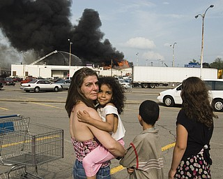 L-R, Youngstown residents Joann Sarbaro, Dreama Williams, 5, Jerome Williams, 9, and Cher-vea Sarbaro, 10, watch the fire from an adjacent parking lot.