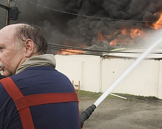 After two hours of battling the fire from the top of a truck, 28-year Youngstown Fire Department Captain Tony Carkido predicted at least another four hours before the area could be deemed safe. Here, Carkido warns other firemen, via radio, that the wall he's hosing may fall any second.