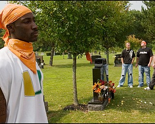 """7.6.2008 Jimmy Hughes Jr, of Youngstown, stands in reflection among fellow motorcyclists paying their respects at the grave of Matthew Adam Tynal, who died from a motorcycle accident on July 1, 2007. """"It makes you feel free,"""" Hughes said of riding motorcycles while donning orange bandannas, the color of Tynal's motorcycle and the motorcycle club, """"The Lost Boyz,"""" found in his honor."""
