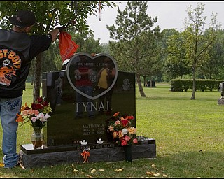 """7.6.2008 Dan Sinclair, of Youngstown, hangs an orange bandanna on the tree beside the grave of Matthew Adam Tynal, who died in a motorcycle accident July 1, 2008. """"The Lost Boyz"""" Motorcycle Club was created in honor of Tynal, choosing the colors of his motorcycle, orange, black and white as their own."""