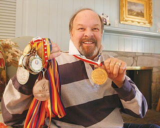 FISTFUL OF MEDALS: Nick Carson of Poland, a dual kidney transplant recipient, shows off the medals he has won in swimming and cycling events at U.S>, World and Australian Transplant Games, including gold he won swimming the butterfly at the World Games in London, Ontario. He will attend this weekend's U.S. Transplant Games in Pittsburgh, but will not compete for health reasons.