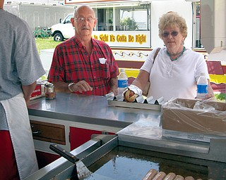 CAN'T WAIT: Ed and Jane Meloni, of Johnston, stand in line for an Italian sausage sandwich at DiRusso's at the Trumbull County Fair. Dominic Fisher, 13, of Canton, served the sausages - made from a family recipe - on the fairgrounds Friday afternoon. Vendors have a variety of foods available for fairgoers to munch on.