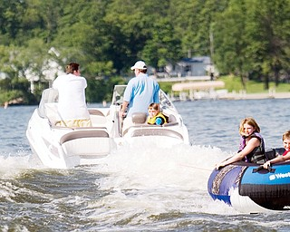 """[7.5.2008] Caylah Mccammon (left), age 8, and John Mccamon (right), age 10, both of Canfield ride in an intertube across Lake Milton July 5, 2008. """"I've noticed more wave runners on the lake,"""" says John Antonucci who mans the wheel of the boat and enjoys being able to take the kids out but admits, """"whipping kids around sure eats up gas."""""""