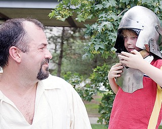 [7.12.2008] Jon Weaver, of Greenville, smiles as Zachary Easton, age 7 of Canfield, tries on a midieval style helmet at a tent belonging to The Society for Creative Anachronism during the ?FESTIVAL OF THE ARTS? along Wick Ave. Saturday afternoon. The group of medieval enthusiasts recreate the tournament style fighting, craft making, drama, music, camping, and cooking of the era citing the importance of learning history beyond simply reading about it and by experiencing it as well. More information can be found at the local chapter's website www.rivenvale.org/ or the national website www.sca.org.