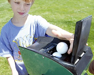 Game on gadget... Andy Garr, 8, of Canfield uses a ball washer while playing in Golf Camp at Mill Creek Park.