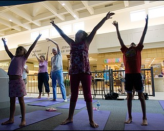 7.17.2008 Michelle Cristo and John Mrofchak, both of Warren, practice Yoga behind Zoe Bowman (7), of Vienna, Anna Cristo (8), of Warren, and Kira Bowman (8), also of Vienna, during Yoga for Kids, a summer workshop at Eastwood Mall offered offered by the Art Outreach Gallery and sponsored by American Gladiators Fitness Center.