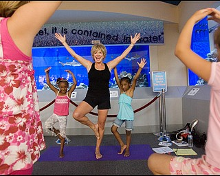 """7.17.2008 Judy Kay, of Howland, practices yoga with participating children during Yoga for Kids, a summer workshop at Eastwood Mall offered offered by the Art Outreach Gallery and sponsored by American Gladiators Fitness Center. """"It has totally changed my life {(I began)} feeling better about life and myself, its keeping me young"""" says Kay of yoga which she has taught for 35 years, """"thats what i want to give back to the kids and you don't need any special equipment you can do it on your own."""""""