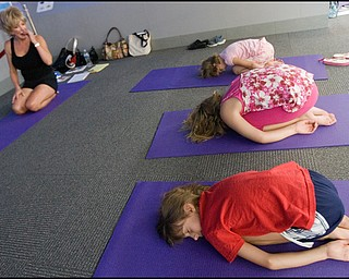 """7.17.2008 (FRONT TO BACK) Kira Bowman (8), of Vienna, Anna Cristo (8), of Warren, and Zoe Bowman, also of Vienna (7), practice yoga before instructor,Judy Kay, of Howland, during Yoga for Kids, a summer workshop at Eastwood Mall offered offered by the Art Outreach Gallery and sponsored by American Gladiators Fitness Center. """"It has totally changed my life {(I began)} feeling better about life and myself, its keeping me young"""" says Kay of yoga which she has taught for 35 years, """"thats what i want to give back to the kids and you don't need any special equipment you can do it on your own."""""""