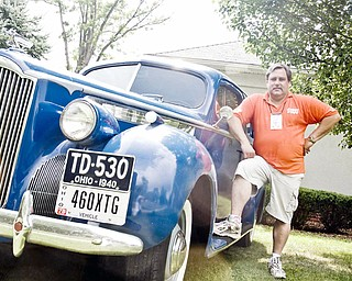 CLASSIC RIDE: Dr. Bob Watson, event organizer for the Packard car show, poses with his electric blue Packard 110 sedan. Walton and fellow auto enthusiasts brought theirs rides to the show Sunday.