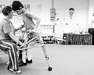 HELPING HAND: Meghan Crowley helps 13-year-old Matthew Mace in an exercise to move his legs during the Miracles Unlimited summer camp. The camp helps children who suffer from motor disabilities.