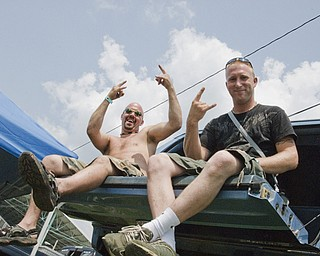 Jason Constantine, 30, of Akron and Matt Evans, 26, of Akron party on the back of Constantine's Monster-sized GMC Suburban at the Canfield Fair Grounds on Sunday, July 27, 2008. Daniel C. Britt.