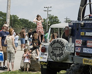 Alexis Liberatore (center, top) of North Lima and her family admires the suped-up trucks from a distance at the Jeep Festival at the Canfield Fair Grounds on Sunday, July 27, 2008. Daniel C. Britt.