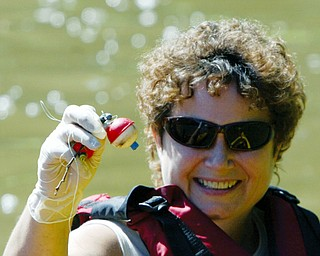 Sue Reniff of Boardman shows a plastic bobber she pulled from Lake Glacier during a clean up effort Thursday by a group of kayakers. wd lewis