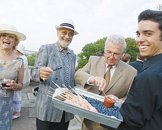 [7.25.2008] Barbara Brothers, Larry Haims, both of Youngstown, and Rolf Nissen, of Warren, enjoy hors d'oeuvres served by Mike Lynch, of Boardman, during a garden party at Fellows Riverside Garden Friday evening.