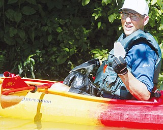 Mark Dolak of Austintown shows a piece of plastic litter he pulled from Lake Glacier in MillCreek Park during a clean up effort by a group of kayakers. WD LEWIS