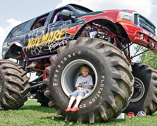 Melody Futchko, 6, of Niles plays on a tire belonging to the nightmare monster truck. At home Melody plays on her power wheels jeep. Jeep Fest, Canfield Fair Grounds on Sunday, July 27, 2008. Daniel C. Britt.