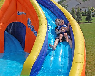 This is a picture of big brother Connor, 10 taking his little brother Dominic, 17 months down a backyard waterslide to cool off.  Picture taken by mom, Kim Yurich of Poland.
