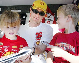 NASCAR driver Kevin Harvick signs autographs for Brooke Cascio, 4, left, and her brother Hunter, 8, at Sharon Speedway Tuesday. They were attending the event with their grandmother Nadine Atkinson of Greenville, Pa.