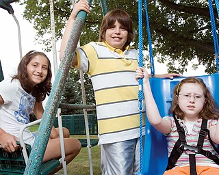 BEING NEIGHBORLY: Twins Kara and Alex Thompson, 11, from left, conducted a fundraiser last month for their neighbor, Sarah Williams, 12, who sits in a special swing in her Poland backyard that her parents bought with donations raised from the benefit.