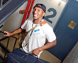 Deaunte Smith, 18, of Cleveland manages a smile as he lugs suitcases up to his dorm in Kilcawley hall. YSU Freshman Convocation on Sunday, August 24, 2008. Daniel C. Britt.
