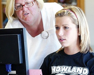Susan Brucoli, Howland yearbook teacher, left, works with student Sarah Stark, 11th grade, in yearbook class at Howland.