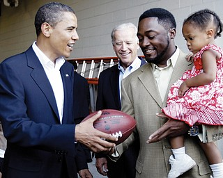 Democratic presidential candidate, Sen. Barack Obama, D-Ill., and his vice presidential running mate Sen. Joe Biden, D-Del., center, gets a football autographed by Pittsburgh Steelers coach Mike Tomlin as he holds his daughter, Harlynn Quinn Tomlin, 2, in Pittsburgh, Pa., Friday, Aug. 29, 2008.