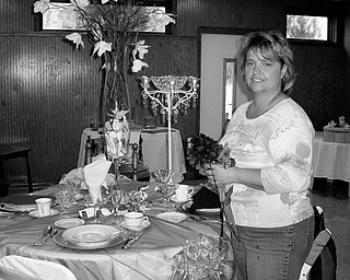 THE BIG DAY: Laurie Dagan, owner of the The Flower Garden Florist and Events by Laurie, works on a wedding reception display in her Warren store. Dagan recently founded the Wedding Network, a local organization for wedding vendors. For more information, go to www.mvweddings.net.