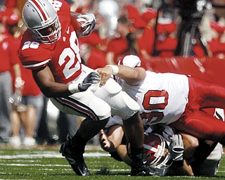 "HEISMAN HOPEFUL HURT: Ohio State running back Chris ""Beanie"" Wells (28) gets pulled down by Youngstown State defender Ben Lane during the first quarter of the Buckeyes' romp in Columbus. Wells injured his leg in the third quarter."
