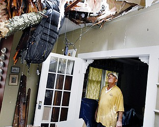 STORM DAMAGE: Richard Bezet looks over damage to the living room of his Baton Rouge, La., home after a tree fell through the roof because of winds from Hurricane Gustav.