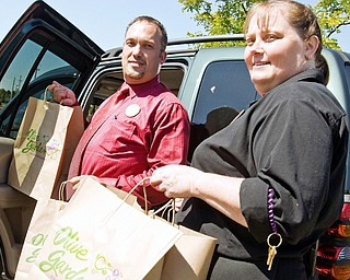 SERVING: Olive garden representatives Ken Jones and Angie Anglin deliver food for a free buffet for workers on labor Day. The Boardman restaurant provided a free lunch for employees at St. Elizabeth in Boardman and the Niles Olive Garden fed the Niles police and firefighters on duty.