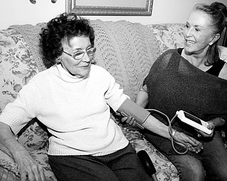 BACK TO WORK: Melissa Fodor, right, who retired from her job as a travel agent has been forced to re-enter the work force as a certified nursing assistant to make ends meet, checks the blood pressure of Lorraine Somme in her home in southwest Denver.