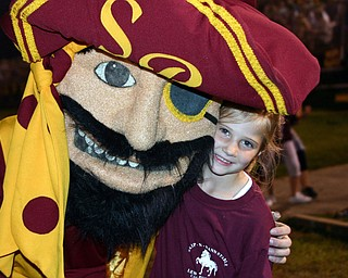 """Little Raider fan Elizabeth Cortwright gets a hug from the South Range mascot."""