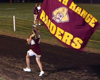 """Varsity Cheerleader, Brittany Haynes, runs the South Range flag after a score."""