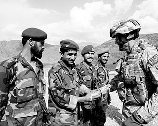 INCREASING OPERATIONS: U.S. Maj. Gen. Jeffrey J. Schloesser, right, shakes hands with Afghan soldiers after arriving at a U.S. base in Nuristan province east of Kabul, Afghanistan. U.S. forces in Afghanistan will increase offensive operations against militants this winter because insurgents are increasingly staying in the country to prepare for spring attacks, the top U.S. commander said.
