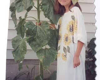 SCRAPBOOK FIND: Patty Gordulic of Canfield found a giant sunflower in her yard. Since she never grew anything before, she was quite shocked. It appears a bird dropped the seed from her feeder. Her niece, Brianna Gordulic, agreed to pose with the sunflower with a sunflower shirt.