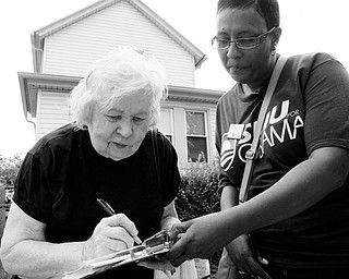 REGISTERING: Linda Graham, right, holds the clipboard as Florence Dziamniski, 82, fills out the voter registration form outside the senior citizen's home in Clairton, Pa. Five days a week, Graham trolls southwest Pennsylvania for unregistered voters, working to add to the big gains Democrats have posted this election cycle. Graham, 45, has taken three months unpaid leave from her job at Pittsburgh's Central Blood Bank to volunteer with Service Employees International Union.