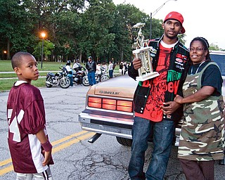 BEST RIDE: Brandon Crosby, 22, of Youngstown, took first place in the car contest at Saturday's Stop The Violence event at Wick Park. Crosby was showing his trophy and his prize-winning 1988 Chevy Caprice, to Stop The Violence organizer Harriett Randolph and young auto enthusiast Ca'Andre Backus, 12, of Youngstown.