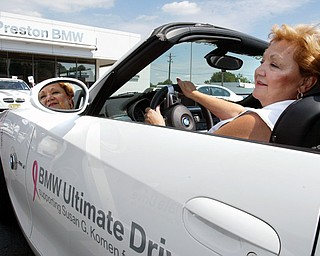 CRUISING: Cancer survivor Dee Pernotto of Campbell test-drives a convertible as part of the BMW Ultimate Drive. The event was Monday at Preston BMW in Warren. BMW donates money to the Susan G. Komen for the Cure organization for breast cancer awareness, research and treatment for every mile driven.