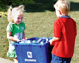 YOUTH MOVEMENT: From left, Keely Sneek, 3, and Logan Flament, 4, both of Poland, carry a bin of recyclables to the curb. Logan's mother, Sarah, is pushing her family to take a more green approach to its lifestyle.