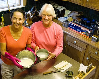 "SHARED EXPERIENCE: Linda Hoefert of Youngstown, left, was taught how to make mozzarella cheese with pesto and prosciutto by Sara Scudier in Scudier's Youngstown home. Scudler belongs to the TimeBank Mahoning Valley, a ""bank"" that takes alternative currency in the form of good deeds tracked by time spent. Scudier deposited an hour by teaching Hoefert."