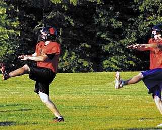 RESUME PLAY: Newton Falls kicker Eric Cooper, left, and quarterback Brian Sole run through drills at hte team's first official practice after a four-day strike suspended the team's workouts. The Tigers were back on the field Wednesday night, just minutes after learning the strike had been settled.