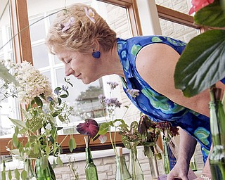 IT'S THE AROMA: Judy Nelson of Columbiana enjoys the smell of a flower at the Garden Forum flower, plant and vegetable show at Mill Creek MetroPark's Fellows Riverside Gardens on Sunday. Nelson said she just happened to stop by the show on a whim.